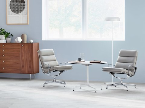 Two light gray Eames Soft Pad lounge chairs and a round Eames Table with a white frame and top.