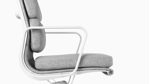 Profile view of a light gray upholstered Eames Soft Pad Chair.
