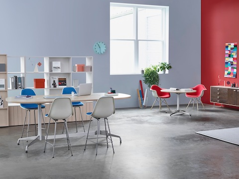 Oval and round Eames Tables in a collaboration area that also features Eames Molded Plastic armchairs and stools in blue and red.