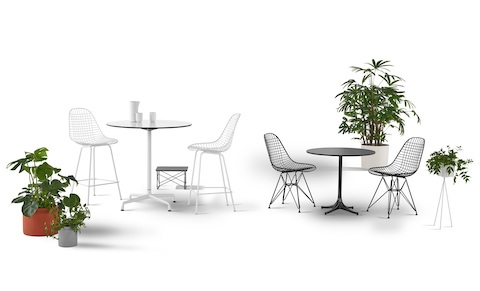 Two round Eames Tables of different heights, one served by two white Eames Wire Stools and one by two black Eames Wire Chairs.