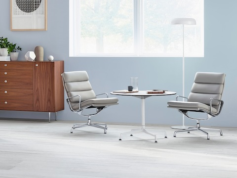 A round Eames Table with a white top, paired with two light gray Eames Soft Pad Chairs.