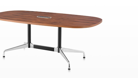 An oval Eames meeting table with a medium wood finish and a central cutout for cord access.