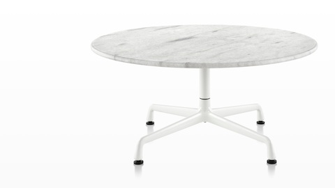 A round Eames Table with a white marble top.