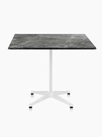 A square Eames outdoor table with a black stone top and white base.