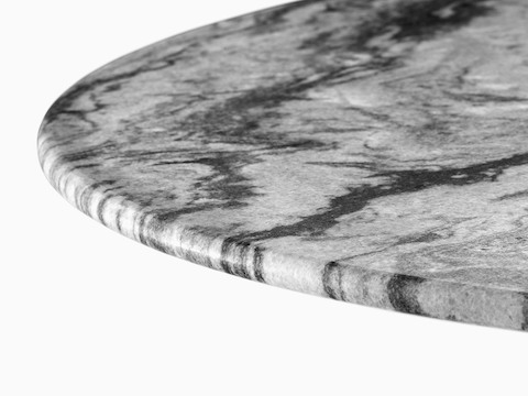 Close view of a round table top made of grey marble, one of four stones available for Eames outdoor tables.