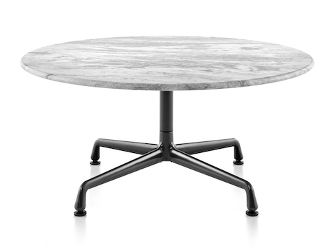 A round Eames outdoor table with a white marble top and black base.
