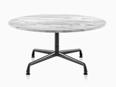 A Round Eames Outdoor Table With White Marble Top And Black Base