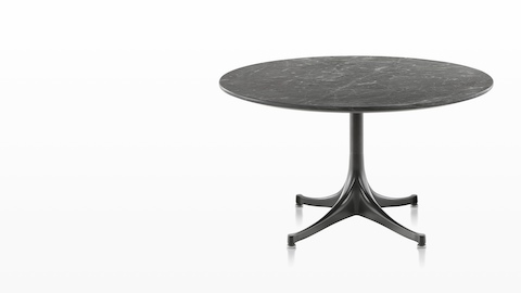 A round Eames outdoor table with a black stone top and black base.