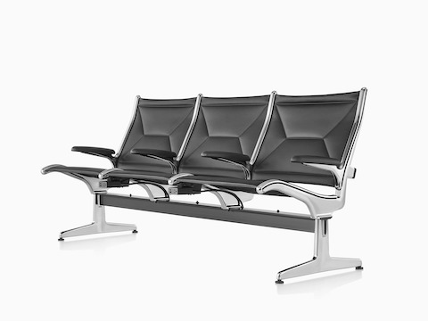 Black Eames Tandem Sling Seating with three seating positions and built-in charging modules, viewed from a 45-degree angle.