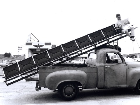 Vintage photo of a man sitting at the end of an Eames Tandem Sling Seating run being delivered via pickup truck.