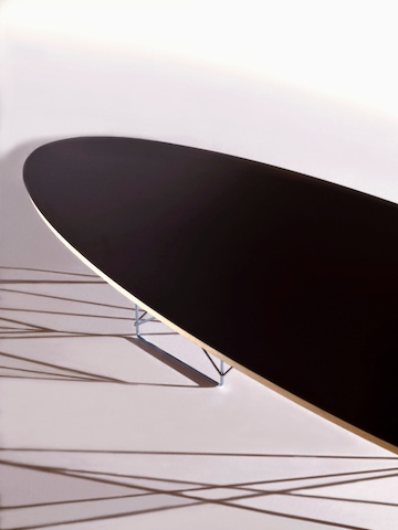 Close view of an Eames Wire Base Elliptical Table with a black top, focusing on the beveled edge.