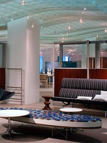 An Eames Wire Base Elliptical Table in an office lobby that also features an Eames Walnut Stool and Eames Sofa Compact.