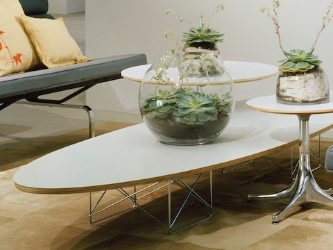 A white Eames Wire Base Elliptical Table nestled with two white Nelson Pedestal Tables.