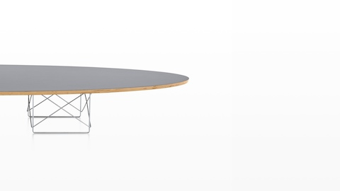 An Eames Wire Base Elliptical Table with a gray surfboard-shaped top.