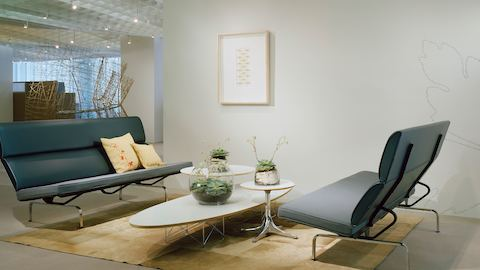An Eames Wire Base Elliptical Table nestled with two Nelson Pedestal Tables and positioned between two  Eames Sofa Compacts.