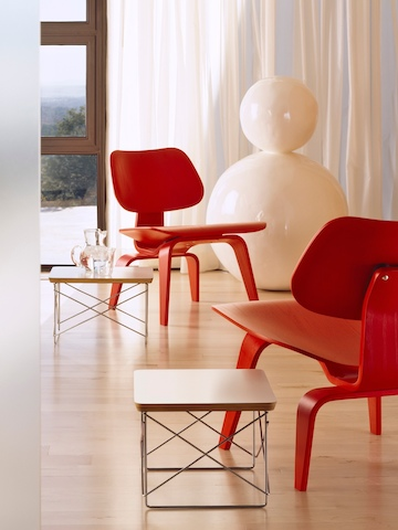 Two Eames Wire Base Low Tables paired with red Eames Molded Plywood Chairs.