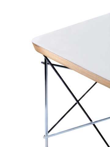 Partial view of a white Eames Wire Base Low Table, focusing on the welded wire rods and beveled top edge.