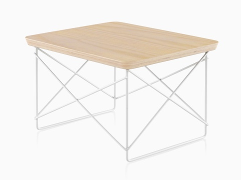 An angled view of an Eames Wire Base Low Table with a white ash veneer top.