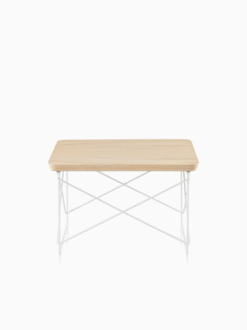 A rectangular Eames Wire Base Low Table with a light wood finish.