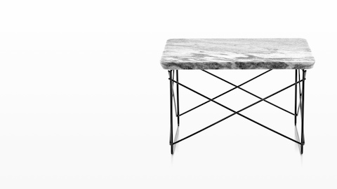 An Eames Wire Base Low Table with a stone top.