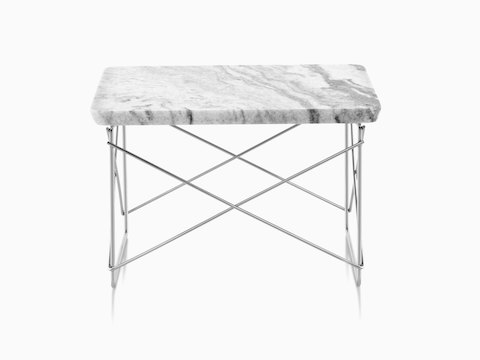 A rectangular Eames Wire Base Low outdoor table with a marble top and silver wire base.