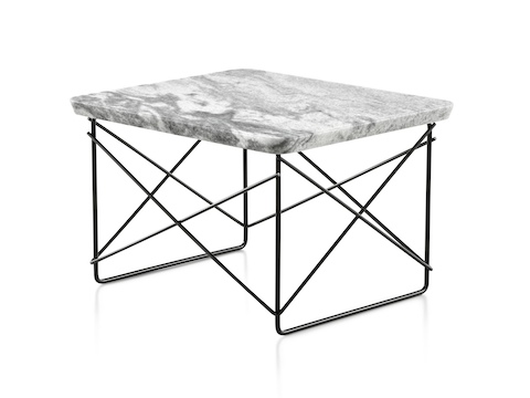 An angled view of a rectangular Eames Wire Base Low outdoor table with a marble top and black wire base.