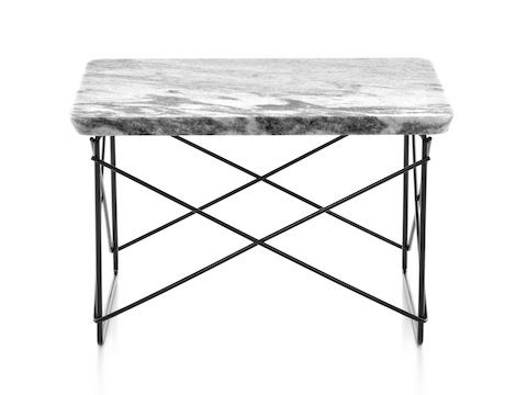 A rectangular Eames Wire Base Low outdoor table with a marble top and black wire base.