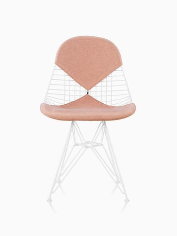 An Eames Wire Chair with a bikini seat and back, upholstered in a light pink textile. Viewed from the front.