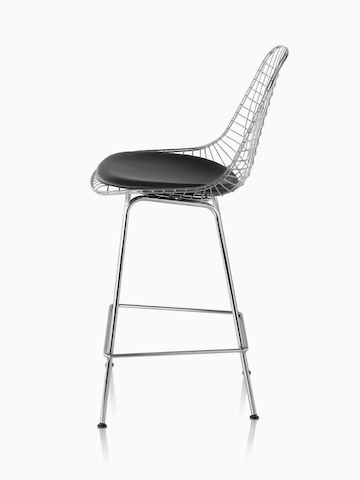 Profile view of a silver Eames Wire Stool with a black seat pad.