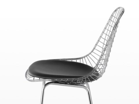 Upper half of a silver Eames Wire Stool with a black seat pad, viewed from the side.