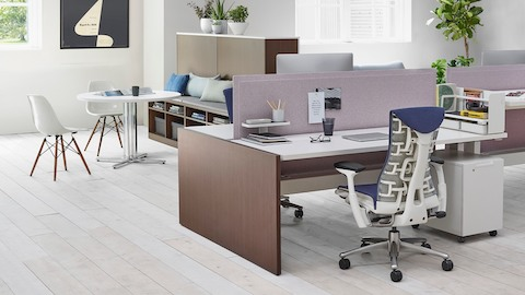 Work setting showing a Blue Embody office chair, wood veneer Renew Link desk, and white Eames Molded Plastic Chairs.