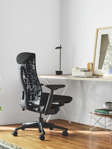 Blue Embody office chair at a black Envelop Desk.