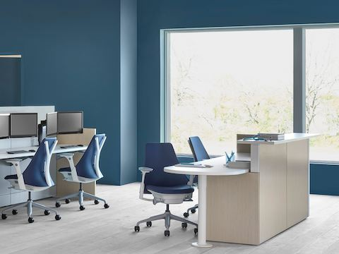 An Ethospace caregiver station in a light wood finish, consisting of a reception desk and a separate workstation with blue upholstered Sayl chairs.