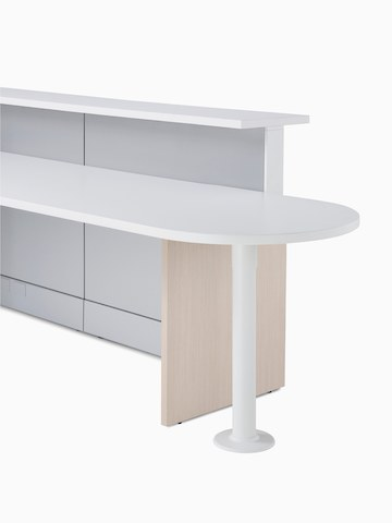 Detail of Ethospace in a light wood finish featuring a round-end ADA peninsula surface, white transaction top, and light gray panels.