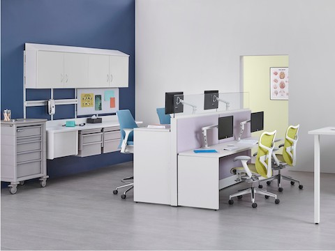 A work environment for healthcare caregivers with seated and standing height workstations and clinical station behind.