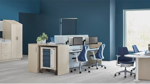 An Ethospace nurse station in a light wood finish, consisting of a reception desk, two-sided workstation for sitting or standing, Mora casework in matching wood, and a supply cart with blue drawers.