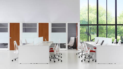 Open workspace with large windows to the outdoors, Ethospace benches, and white Sayl office chairs with red upholstered seats.