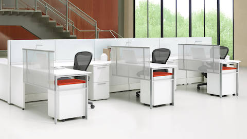 White Ethospace workstations with low dividing panels, fabric dividing screens, and black Aeron desk chairs.