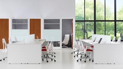 White Sayl desk chairs with red upholstered seats at Ethospace benches in an open office.