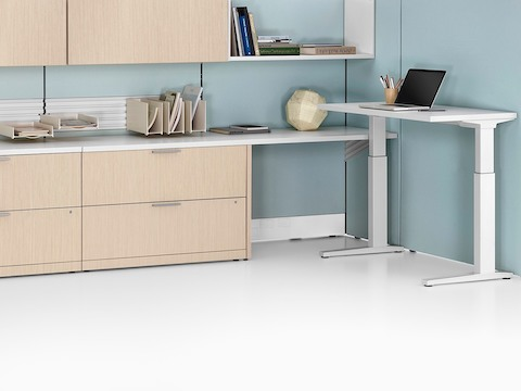Ethospace workspace with high dividing walls, low and high lateral storage units, and height-adjustable desk.