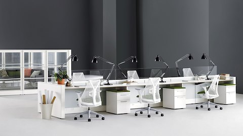 Open workspace with Ethospace benching system, Sayl chairs with white backs and forest green upholstered seats, and task lighting.
