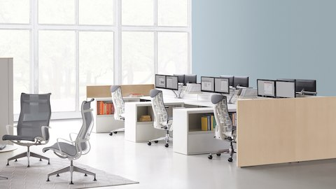 Gray upholstered Embody ergonomic desk chairs at Ethospace workstations with monitor arms in an open office near a lounge with Setu Lounge Chairs.
