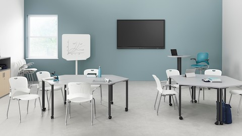 Two pairs of white trapezoidal Everywhere Tables arranged in a learning environment, with white Caper stacking chairs.