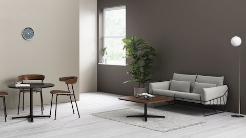 Two Everywhere Tables in an informal seating area, with wooden Leeway Chairs and a grey Wireframe Sofa.