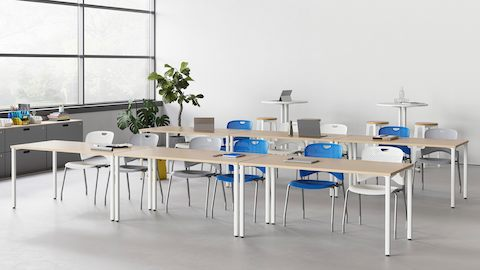 A learning environment featuring two rows of Everywhere Tables and Caper stacking chairs in various colours.