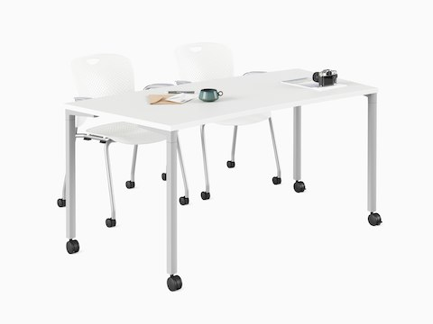 White classroom curve Everywhere Table with a pair of Caper stacking chairs.