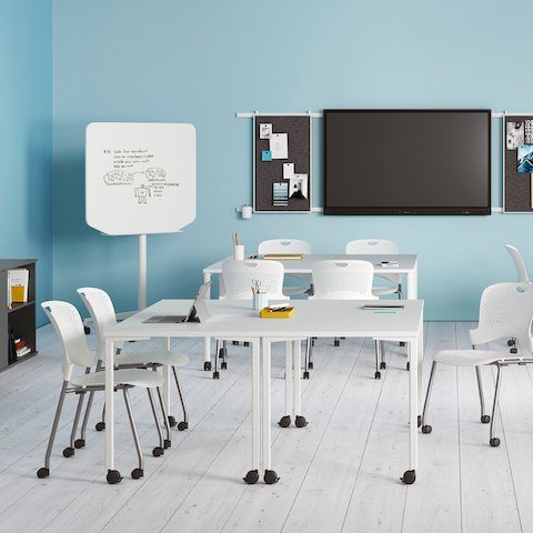 Everywhere Tables in a learning environment, including rectangular and round standing height options with white Caper Stacking Chairs.