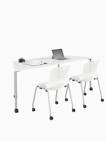 White trapezoid Everywhere Table with a pair of white Caper stacking chairs. Select to go to the Everywhere Tables product page.