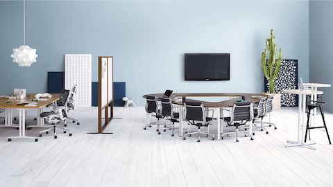 A café-height Everywhere Table provides collaboration space for a workstation that also features a blue Embody office chair.