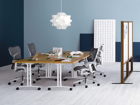 Three white leather Eames Soft Pad Chairs around a rectangular Everywhere meeting table in a dark wood finish.
